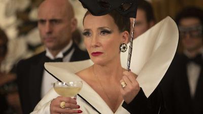 Närbild på baronessan Hellman (Emma Thompson) med ett champangeglas i handen.