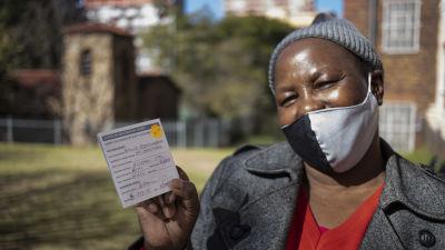 En kvinna i Johannesburg i Sydafrika visar upp sitt intyg på att hon har fått två doser coronavaccin.