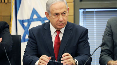 Benjamin Netanjahu ser fundersam ut med Israels flagga i bakgrunden.