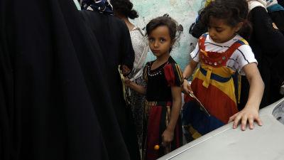 Två barn köar för att få mathjälp i svältdrabbade Jemen