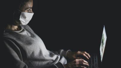 Kvinna med munskydd över näsa och mun sitter i mörkret och skriver på bärbar dator.
