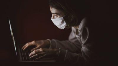 En kvinna med munskydd sitter i ett mörkt rum och tittar på en datorskärm