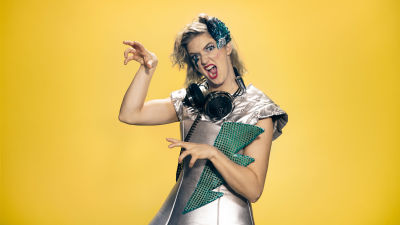 Programledaren Lisa Gerkman i Lady Gaga inspirerad outfit poserar med händerna som klor. Gul bakgrund.