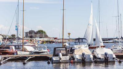 En gästhamn full av motor- och segelbåtar. Himlen är klarblå.