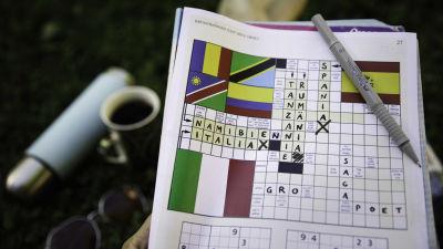 En tidning är vikt så att en sida med ett korsord syns. En penna vilar på tidningen och korsordet är delvis ifyllt. Orden Namibia, Italia, Spania, Tanzania och Rumänia är skrivna.