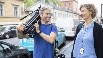 A photograph in a blue shirt carries a camera tripod and talks to a journalist in a blue shirt.