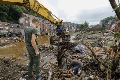En soldat står och betraktar förödelsen i Belgien efter översvämningar. Fler personer deltar i röjningsarbetet.
