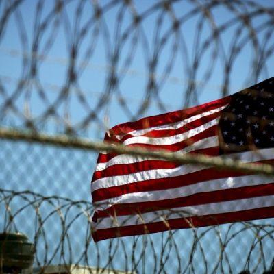 Yhdysvaltain lippu liehuu Guantanamon piikkilanka-aidan takana.