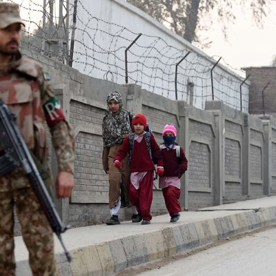 Pakistanilaisia sotilaita seisoo kaduilla vartiossa, kun lapset kävelevät kouluun Peshawarissa.