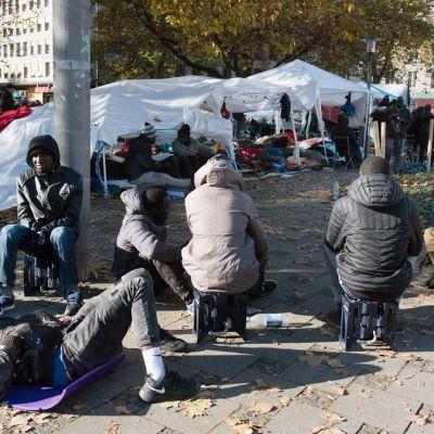 Afrikkalaisia miehiä istuskelee teltan ulkopuolella Münchenissä Saksassa.