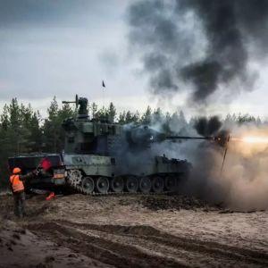 En pansarvagn skjuter, det kommer eld ur pipan. Två män med orangea västar står bredvid.