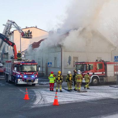 Flera brandbilar och brandmän framför trähuset i Björneborg som brinner 5.11.2016.
