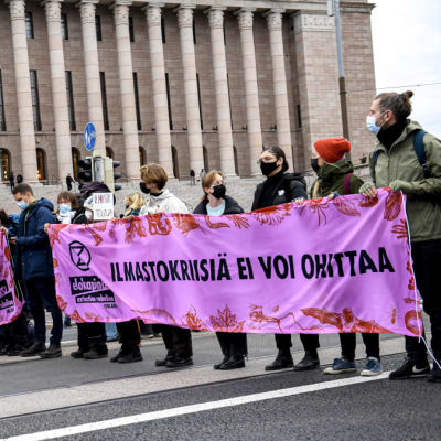 Demonstranter som står på Mannerheimvägen och håller upp en banderoll.