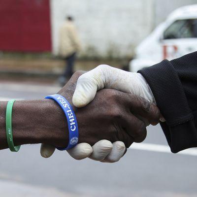 Mies kättelee toista suojakäsine kädessään 28. heinäkuuta.