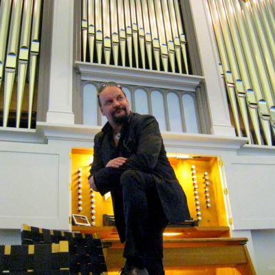 Kalevi Kiviniemi seisoo Hämeenlinnan kirkon urkujen edessä
