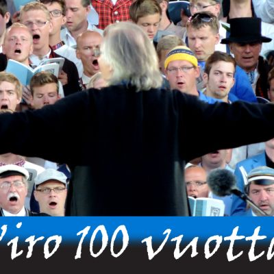 Kuoronjohtaja selin ja kädet levällään laulavien miesten edessä.