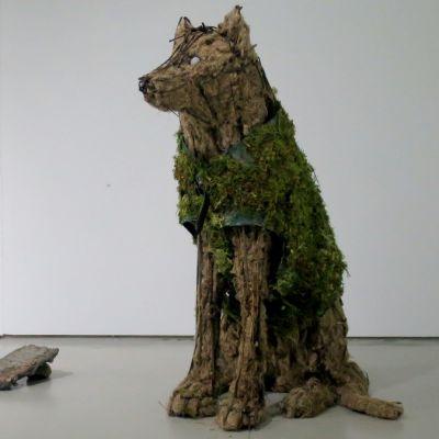 Istuvan suden näköinen patsas joka on tehty rautakehikosta, hampusta ja suojaliivistä