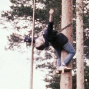 Turppi-ryhmän jäsen roikkuu puussa performanssissa Lehtimäellä.