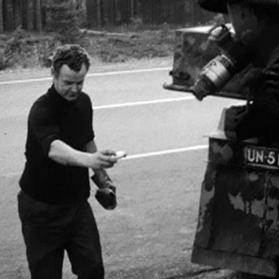 Loka-auton kuljettaja ripottelee suolaa likaveteen.