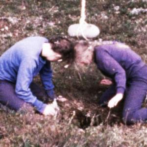 Turppi-ryhmän jäseniä polvillaan köydessä roikkuvan kiven alla performanssissa Lehtimäellä.