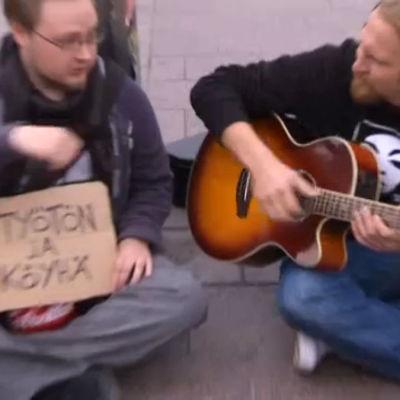 """Paleface soittaa kitaraa. Vieressä mies, jolla kyltti """"työtön ja köyhä"""""""