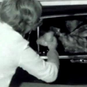 Nainen tarjoilee autossa istuvalle miehelle nakkisämpylän ohjelmassa Kamera kiertää (1968)