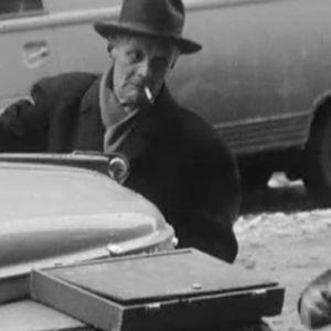 Miehet yrittävät avata auton konepeltiä.