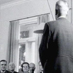 Mies seisoo mustavalkoisessa kuvassa ihmisjoukon edessä