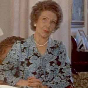 Sopraano Aulikki Rautawaara istuu pöydän ääressä. Kuvassa oikealla valkoisia neilikoita.
