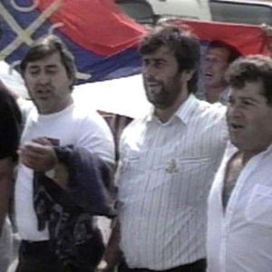 Serbimiehiä kävelemässä kadulla lippu mukanaan