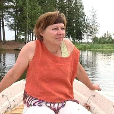 Anna-Leena Ilmarinen istuu soutuveneessä Hulkkianjärvellä.