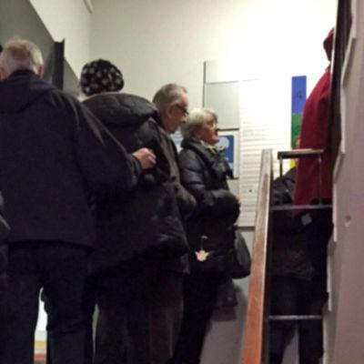 Påklädda helsingforsare köar i en trappuppgång på Femkantens hälsovårdscentral.
