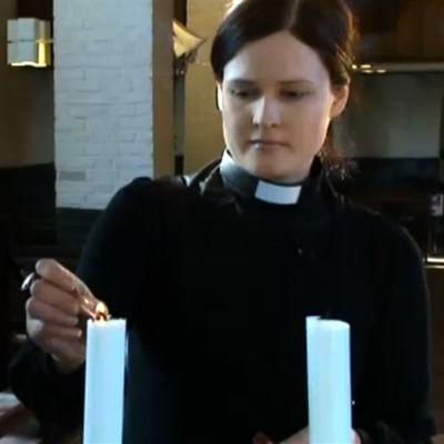 Pappi Mari Leppänen sytyttää kynttilää kirkossa, ohjelmasta A-Studio 6.3.2012