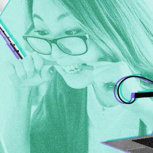 Nainen pureskelee kynää tietokoneen ääressä