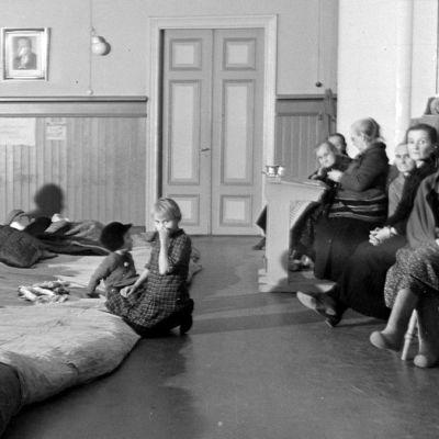 Aikuisia ja lapsia tilapäisine peteineen koulun lattialla