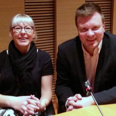 Aino-Kaisa Pekonen ja Ville Skuinnari katsovat kameraan kokoushuoneessa