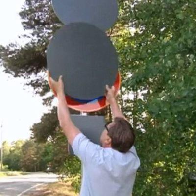 Mies nostaa harmaata levyä pois liikennemerkin päältä.