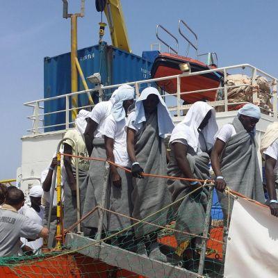 Huopiin kääriytyneitä ihmisiä kävelee laivasta pois.