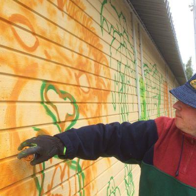 Samuli Turunen maalaamassa graffitia.