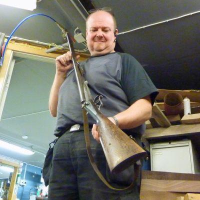 Aseseppä Markku Tiihonen kädessään noin sata vuotta vanha haulikko