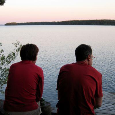 Nainen ja mies istuvat järvenrannalla erikseen.