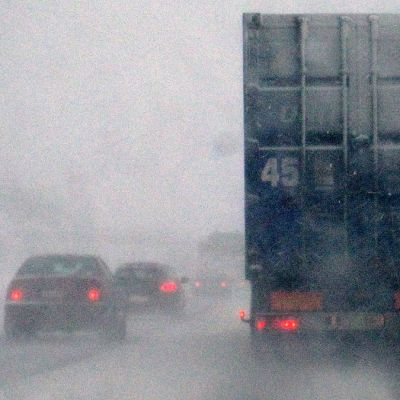 Autoja ohittamassa rekkaa lumipyryssä