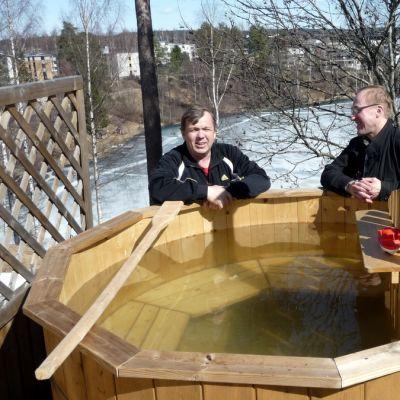 Keijo Hakulinen ja Ilmo Koivisto seisovat kylpytynnyrin takana.