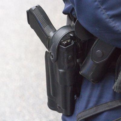 Poliisin virka-ase vyöllä.