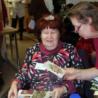 Nainen yllättyy kun hänen ojennetaan postikortti