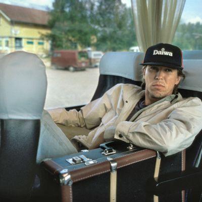 Martti Suosalon esittämä Sepeteus linja-autossa matkalaukun kanssa