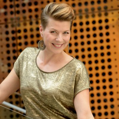 Laulaja Heidi Kyrö seisoo Verkatehtaan portaissa ja katsoo kameraan