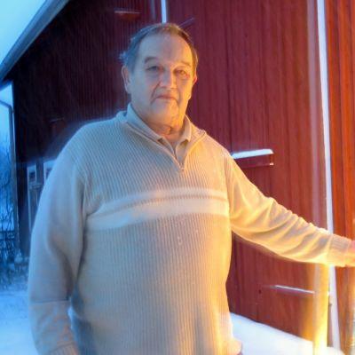 Mies lumisateessa vanhan navettarakennuksen vieressä jouluvalojen kanssa