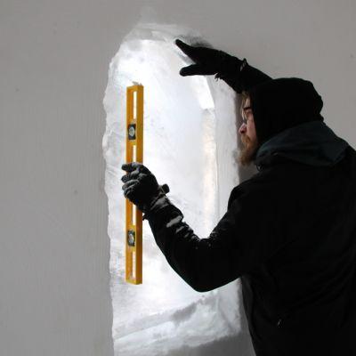 Mies sentaa lumikirkon jääikkunaa