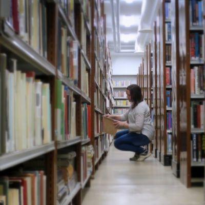 Nainen istuu kyykyssä kirjahyllyjen välissä